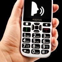 Kapsys Minivision. En hånd som holder telefonen. Den er hvit med store taster og med god kontrast.