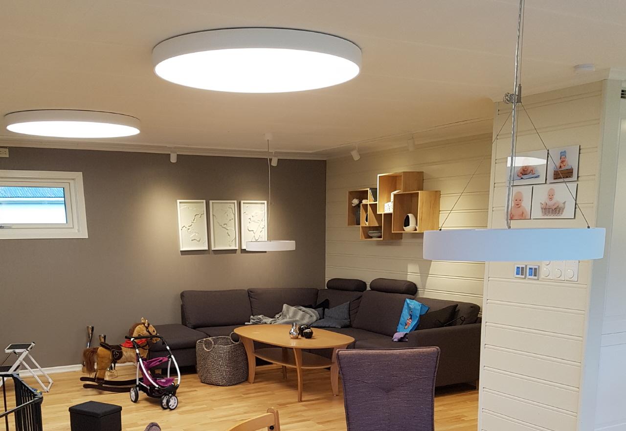 Viser en stuekrok med store lamper i taket som lyser godt opp.