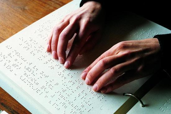 Person som leser punktskrift med begge hender.